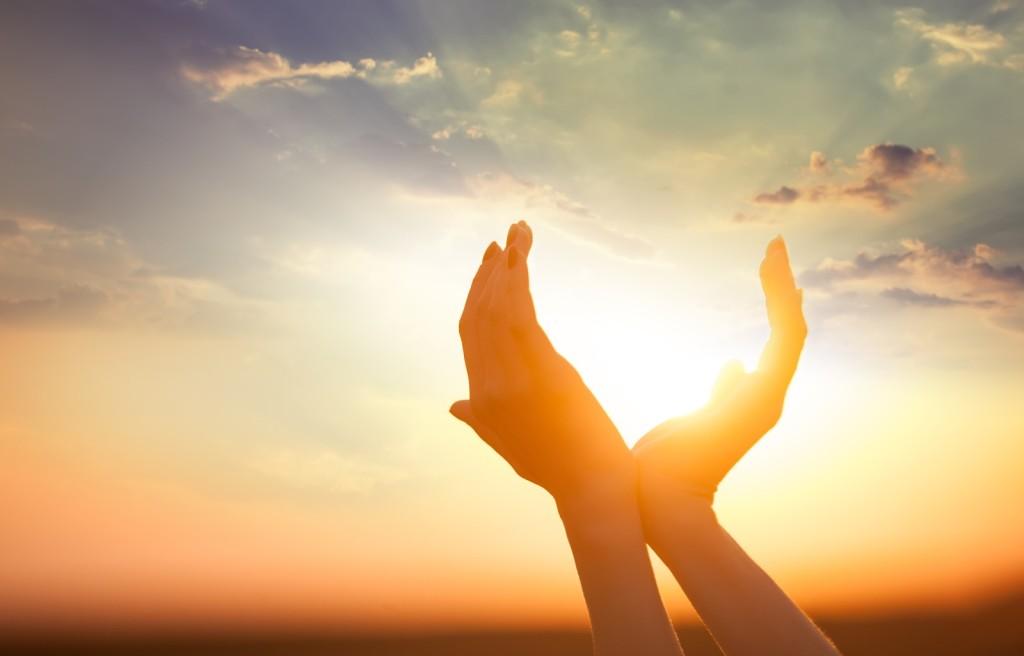 Handen en zon vormen een hart